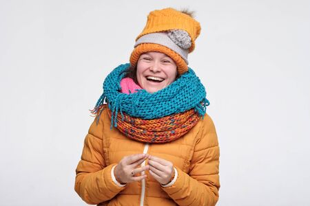 Playful cute winter woman in scarfs and hat having fun laughing. Cute caucasian girl is happy that winter is near isolated on white background. Stockfoto