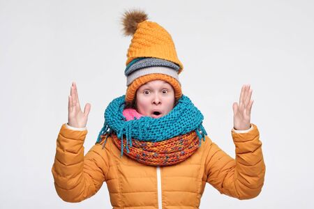 Young woman wearing several hats and scarfs on winter day shows medium size with hands Stockfoto