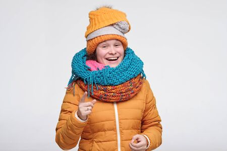 Playful cute winter woman in scarfs and hat pointing at camera laughing on her friend joke. Cute caucasian girl is happy that winter is near isolated on white background. Stockfoto