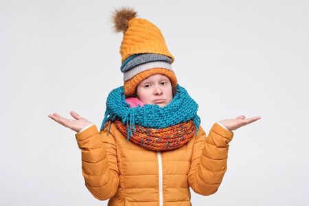Young woman in warm winter hat and scarf shrugging shoulders over white background