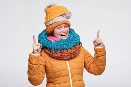 Funny young woman in warm winter hat and scarf smiling pointing up showing copy space on white background.