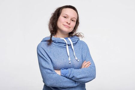 Caucasian confident woman in blue clothws smiling standing with folded hands. Studio shot. Positive facial human emotion.