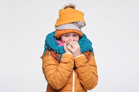 Funny young caucasian woman wearing several warm winter hats and scarfs being afraid biting nails. Studio shot Stockfoto