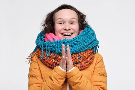 Caucasian funny woman in many scarfs being excited with gift. Studio shot