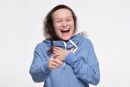 Caucasian female teenager in blue clothes laughing at you pointing with finger. You are so funny. Studio shot Stockfoto