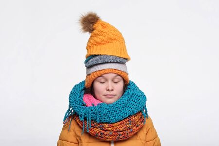 Funny caucasian female teenager in several scarfs and hats relaxing with closed eyes. Studio shot