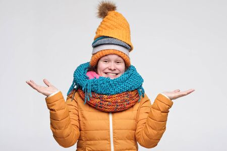 Cute caucasian woman in warm scarf and hats saying it happened anyway. Look here on copyspace. Studio shot