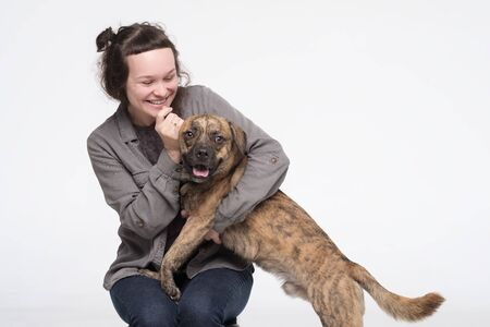 Young pretty woman embracing her dog. Friendship between man and domestic pet. Studio shot