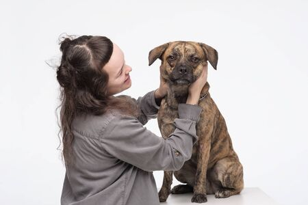 Young pretty woman embracing her dog. Happy owner hugging his best friend pet. Studio shot