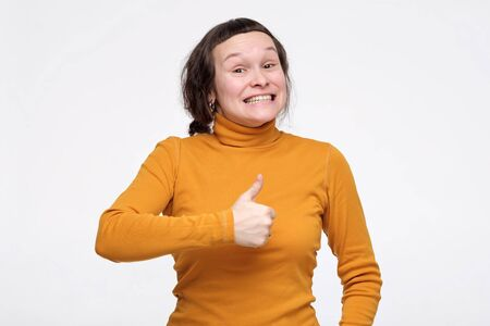 Happy excited woman showing thumb up approving your choice. Human facial emotion. Studio shot