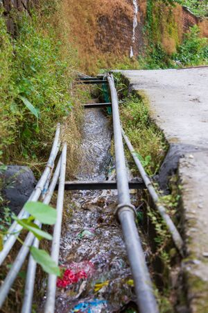 Water flow in polluted drainage stream in indian village with pipes. Reklamní fotografie