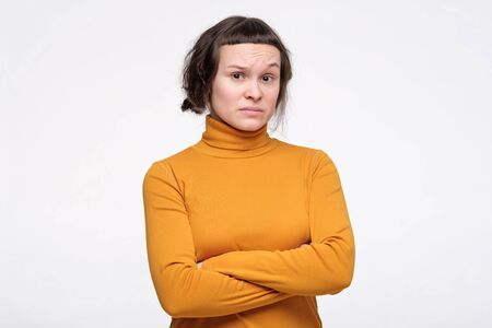 young woman in yellow clothes keeping arms folded, having distrustful suspicious look