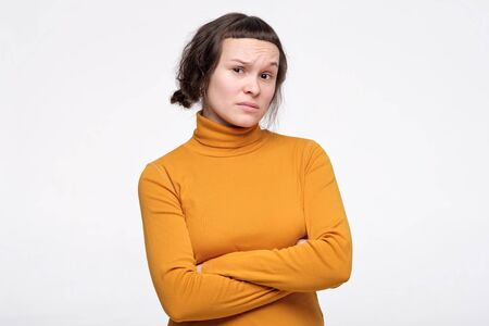 Displeased skeptic young woman in yellow clothes keeping arms folded, having distrustful suspicious look