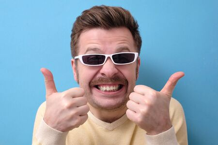 Funny caucasian man with retro mustache and sunglasses giving a thumbs up