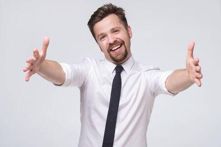 Collègue avec moustache tirant les mains vers la caméra et souriant amicalement à la caméra voulant un câlin Banque d'images