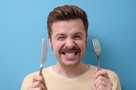 Crazy, starving man with mustache holds a knife with a fork in his hands, grins. I am starving concept.