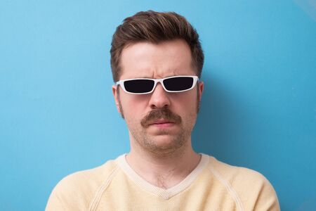 geek retro caucasian man with funny mustache sunglasses with serious emotion on face