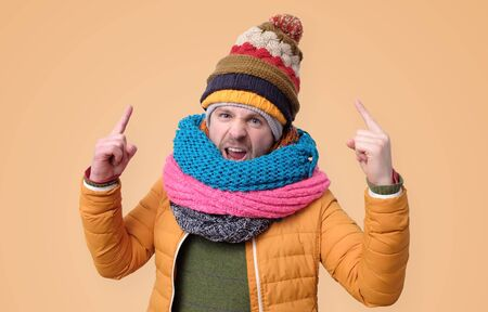 Strict mature man in winter scarf and hat showing index fingers up 版權商用圖片