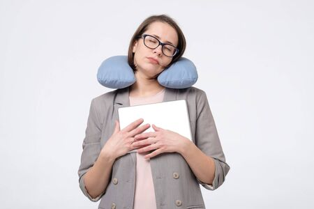 Caucasian matur woman in glasses resting with travel pillow in vacation trip