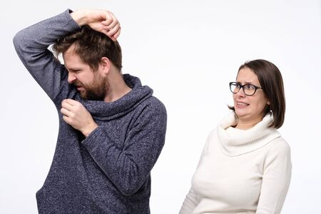 Young man with sweat stain on his clothes and caucasian woman feeling bad smell.