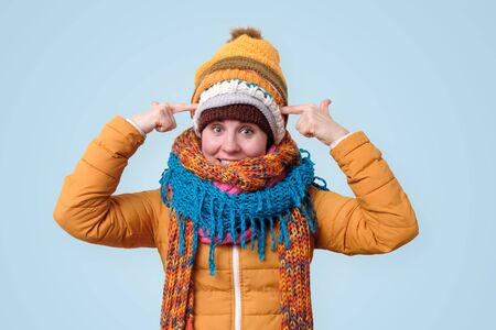 Creative caucasian woman in several scarfs and hats create new concepts, pondering ideas, have great plan.
