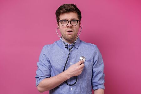 Serious caucasian worried man listening to his heart with stethoscope