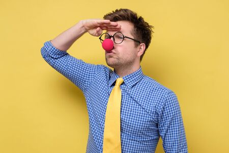Millennial man in clown clothes with red nose and glasses looking aside far away on yellow wall.