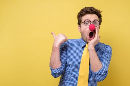 Shocked man with red clown nose looking camera showing pointing on copyspace. Clown, corcus or show concept.