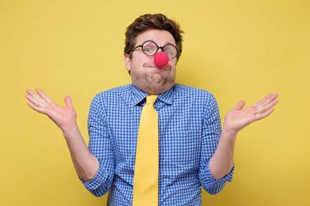 Jeune homme clown drôle avec nez rouge et cravate jaune montrant l'ignorance Banque d'images