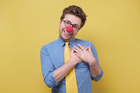 Cheerful clown man with red nose smiles happily, keeps hands on chest, expresses his positive emotion Foto de archivo - 138300191
