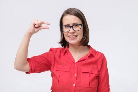 Femme mature à lunettes et chemise rouge montrant quelque chose de petit et minuscule avec un geste et l'air choqué