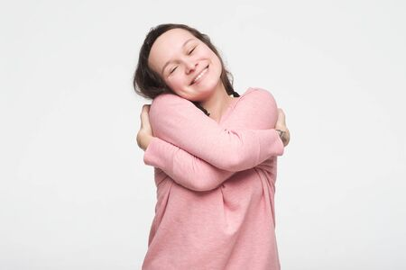 Pretty caucasian teenager in pink clothes hugging herself being proud feeling comfortable.