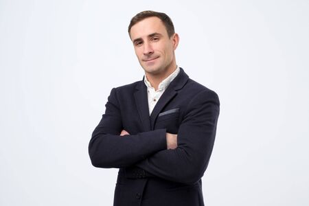 Confident italian mature man with folded hands looking at camera.