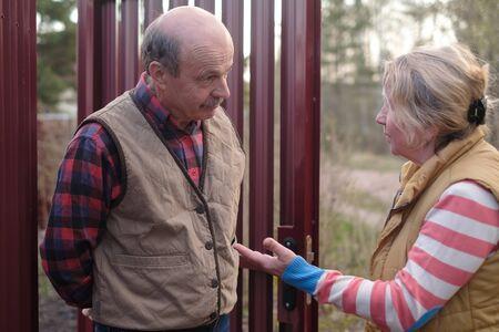 Retired woman talking to a senior man near fence.