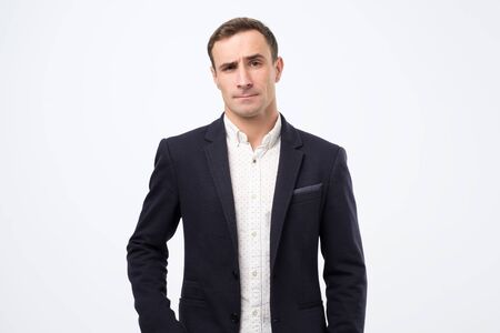 Puzzled european man in suit wears fashionable clothes, raises eyebrows in bewilderment, has to make difficult life choice, lookes confused. Studio shot