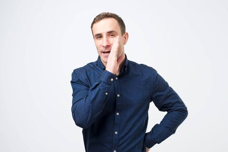 Young man in blue shirt whispering telling gossips and rumors. Studio shot