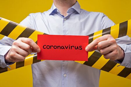Caucasian man holding a banner with word coronavirus on yellow background. Virus pandemic protection and quarantine cConcept