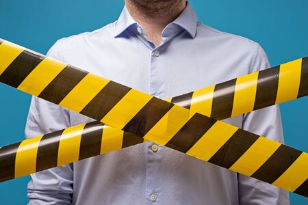 Man standing behind black and yellow lines of barrier tape that forbids passage. Concept of No entry. Protection from coronavirus. Imagens