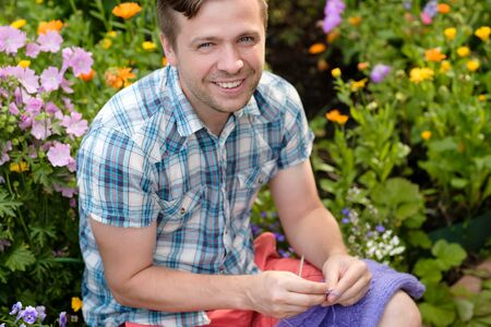Young caucasian man hand study knitting with needles.