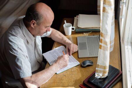 Senior man is writing in his room sitting near window.