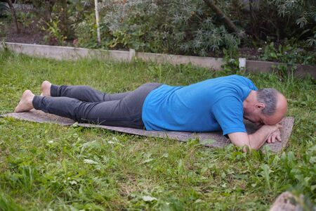 Sporty senior man resting after yoga, fitness, pilates practice lying on mat on grass Stock Photo