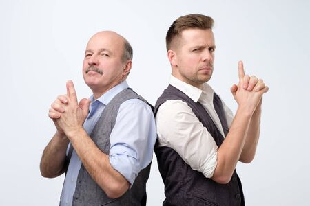 Two caucasian businessman doing a gun gesture getting ready to shoot and acting like a secret agent Stockfoto