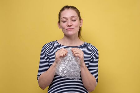 Woman bursts bubbles on a packaging wrap, trying to calm down.