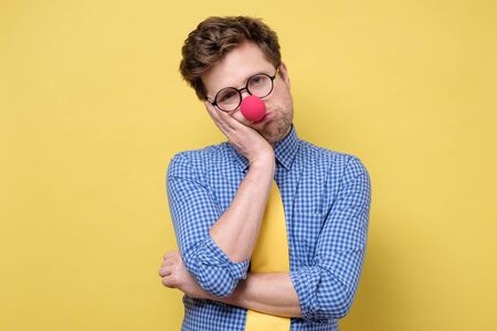 Very bored adult man with red clown nose holding hand on cheek while support it with another crossed hand, looking tired and sick, after party. First April or Fool Day concept. Stock Photo