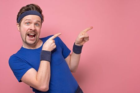 Excited sportive young man in blue t-shirt and hair band cheering and pointing on copyspace on pink background