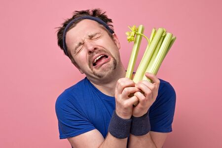 Funny handsome sporty man with mustache holding fresh celery crying. Standard-Bild