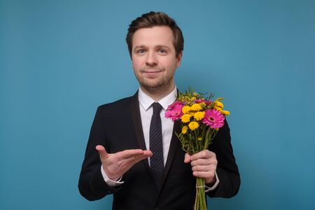 Young caucasian man in suit holding flowers as gift for girlfriend proposing.