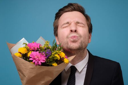 Funny attractive adult man holding flower bouquet folding lips while waiting for kiss