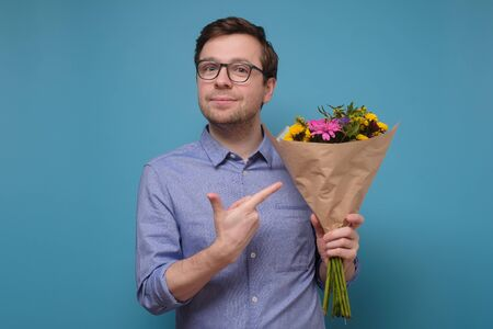 Young caucasian man in pink t-shirt holding flowers as gift for his mother or girlfriend