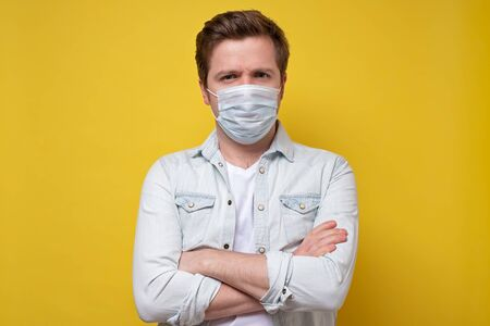 Caucasian young doctor wearing medical mask trying to protect from flu or coronavirus. Zdjęcie Seryjne